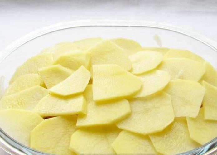 Разложите кружки картофеля на курицу с луком в виде черепицы.