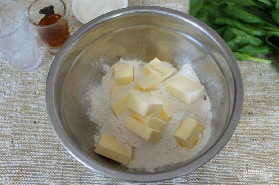 В миску насыпаем муку и добавляем холодное сливочное масло, нарезанное кусочками. Разминаем.
