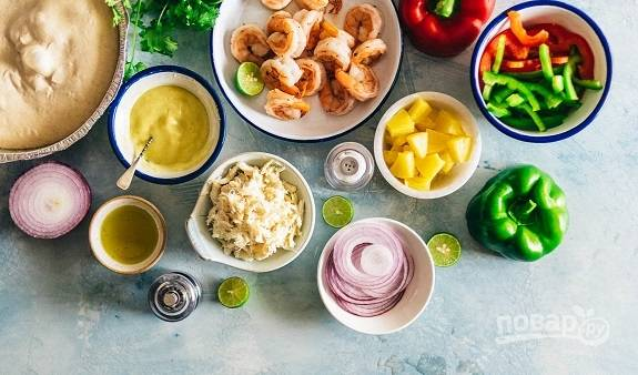 1. Ингредиенты, которые мы будем использовать. Духовку первым делом включите и разогрейте до 200 градусов. На сковороду налейте оливковое масло, отправьте туда креветки. Добавьте соль и перец. Обжарьте несколько минут, помешивая, до готовности.