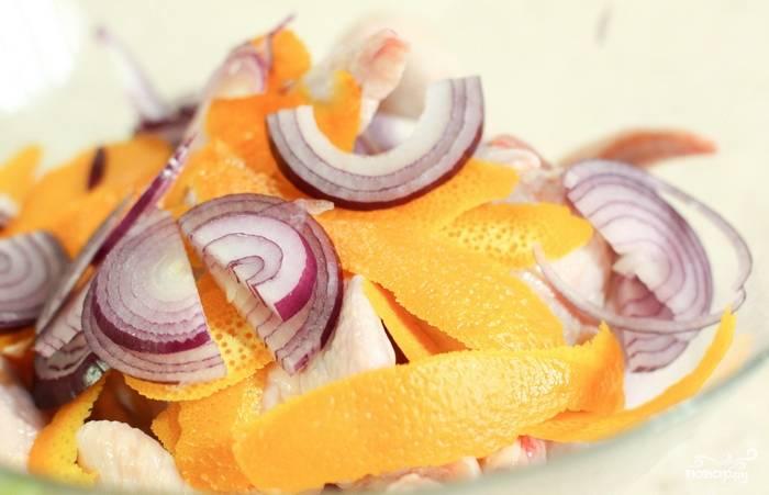 1. Промойте крылышки в холодной воде, а после высушите их бумажным полотенцем. Нарежьте лук полукольцами, а с апельсина срежьте цедру. В большой миске сложите крылышки, цедру и лук.