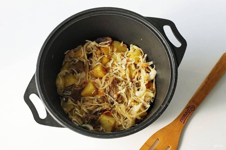 Добавьте капусту, все перемешайте и тушите на небольшом огне до готовности картофеля. Можно добавить в процессе примерно 0,5 стакана воды. Периодически необходимо перемешивать.