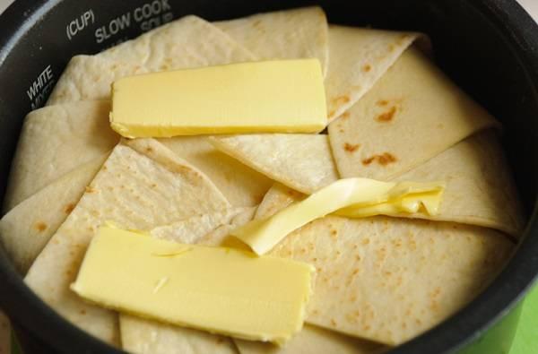 12. Аккуратно свернуть свободные кусочки лаваша вверх и выложить пару небольших кусочков сливочного масла. Отправить форму (можно предварительно дно и бока также смазать маслом или застелить бумагой, например) в разогретую духовку примерно на 45-50 минут.