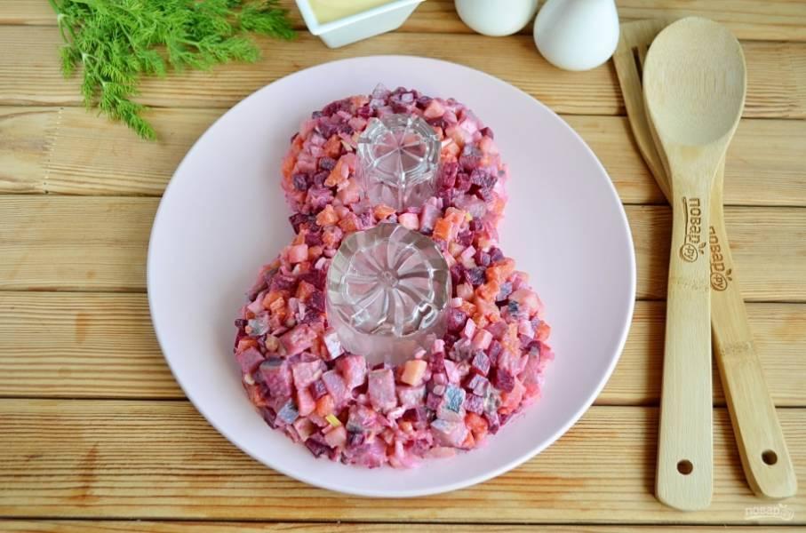 Возьмите большое блюдо. Поставьте на него два стакана разного диаметра. Вокруг стаканов выкладывайте салат в виде восьмерки.