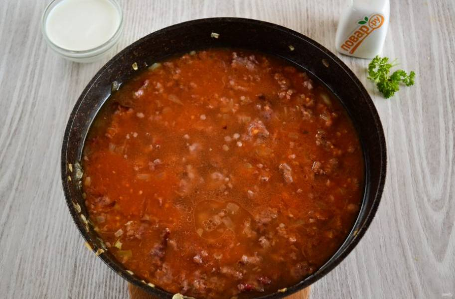 Когда фарш обжарится и начнет золотиться, добавьте в сковороду томатный сок. Он у меня достаточно жидкий, поэтому я увариваю его с фаршем до легкого загустения. Если томатного сока у вас нет, можно развести примерно 1,5-2 ст.л. томатной пасты в 400 мл. воды.