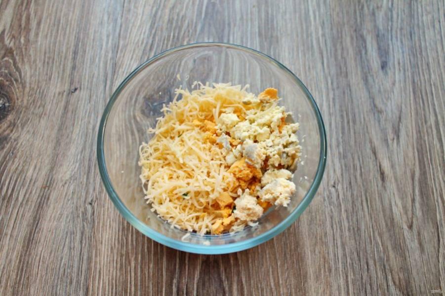 Сыр натрите на мелкой терке выложите в миску. Желток измельчите и добавьте в миску с сыром, перемешайте.