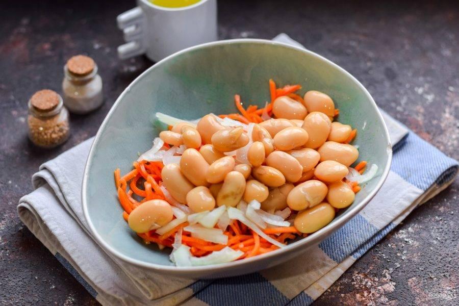 Переложите в салат консервированную фасоль.