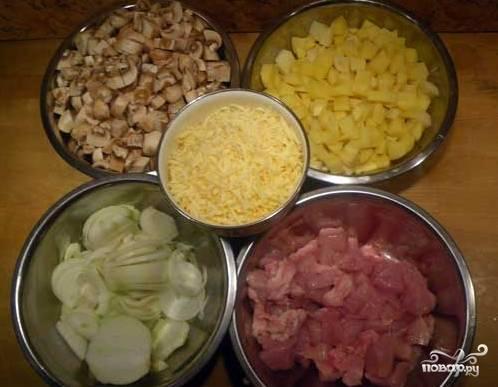 Картофель и курицу нарежьте небольшими кубиками, лук – полукольцами, а сыр натрите на крупной обычной терке.