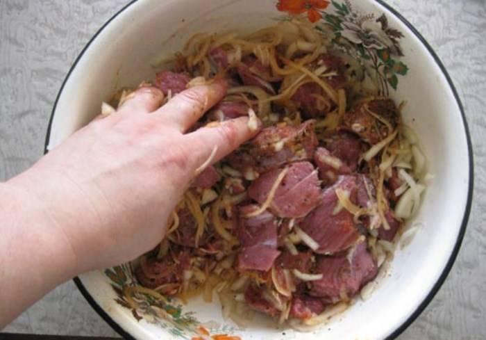 Затем добавьте в мясо очищенный чеснок и две столовых ложки масла. Хорошо разомните мясо с луком и специями.