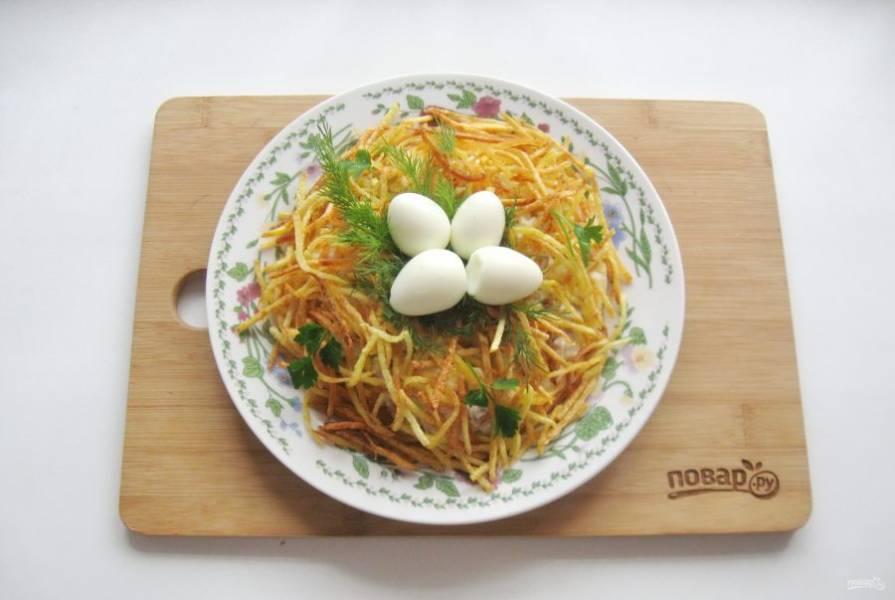 Выложите салат на тарелку горкой. Сделайте в середине углубление. Покройте салат картофельной жареной соломкой. В углубление выложите вареные перепелиные яйца. Украсьте зеленью.