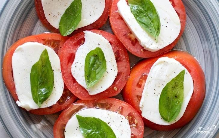6. Подсолите закуску немного, добавьте щепотку перца, сбрызните оливковым маслом. Вот и весь секрет, как приготовить помидоры с моцареллой и базиликом. Угощайтесь!