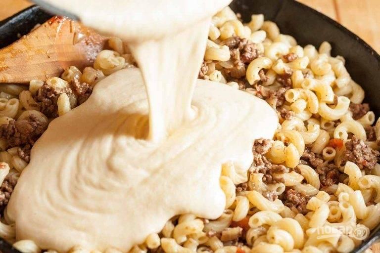6.В сковороду к овощам и фаршу добавьте макароны, перемешайте, влейте приготовленный соус.