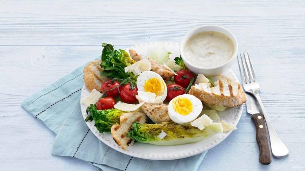 Яйца очистите и порежьте на половинки. Соберите салат, выложив на тарелку все ингредиенты. Сверху положите кусочки пармезана и подайте салат с заправкой.