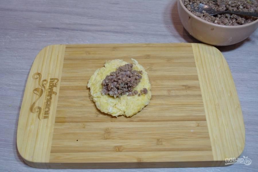 На серединку картофельной лепешки выложите  мясную начинку. Соедините края лепешки и сформируйте колобок.
