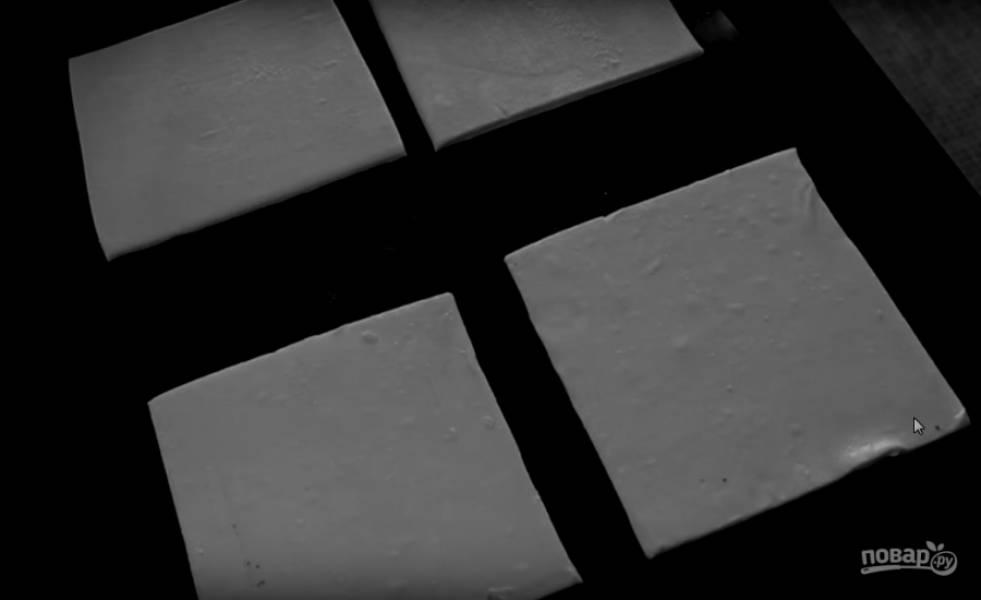 1. Для начала слегка размораживаем тесто и режем на четыре ровных квадрата.