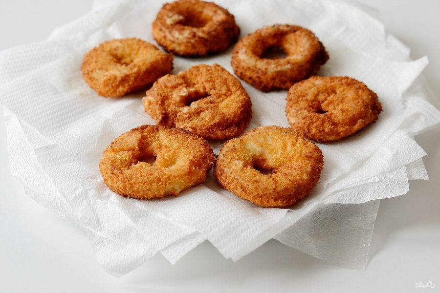 Далее опустите кольца лука во фритюр и обжарьте пару минут. Готовые кольца выложите на бумажные салфетки, чтобы впиталось лишнее масло.