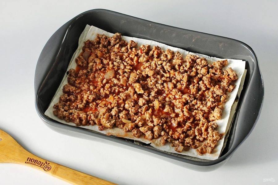 Накройте третьим листом лаваша и распределите оставшуюся начинку.