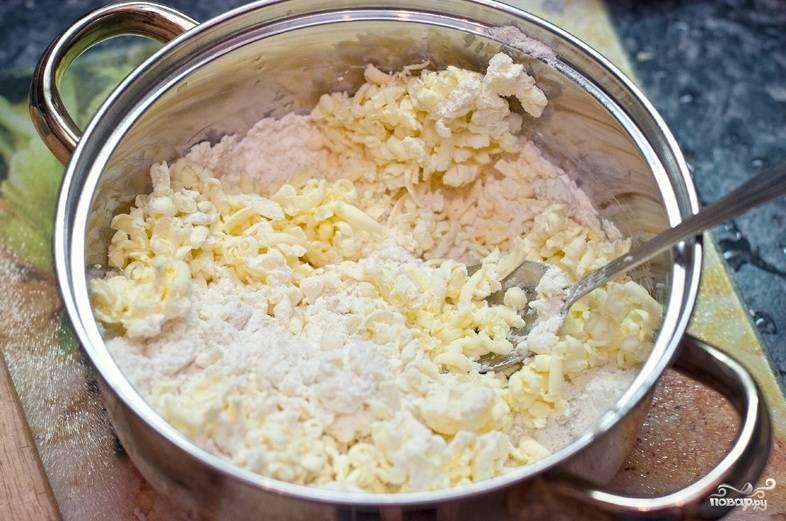 Миндаль перемолотите в крошку. Добавьте к 1/3 орехов 2 ст. ложки сахара, 6 ст. ложек муки. Также натрите на крупной тёрке 120 гр. масла. Размешайте, добавьте одно яйцо, замесите тесто. Уберите его в холодильник на 30 минут.