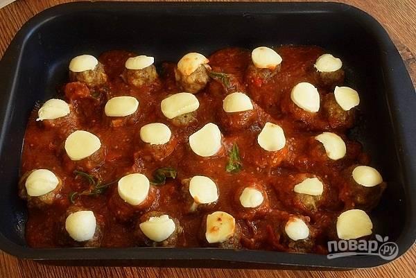 Залейте соусом румяные фрикадельки, сверху выложите моцареллу, нарезанную на тонкие ломтики, и продолжайте запекать еще 8 минут до расплавления сыра.