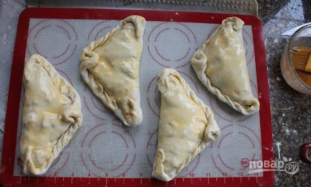 9. Выложите пирожки на противень, застеленный пергаментом или силиконовым ковриком. Смажьте верх оставшимся яйцом, отправьте в разогретую до 180 градусов духовку.