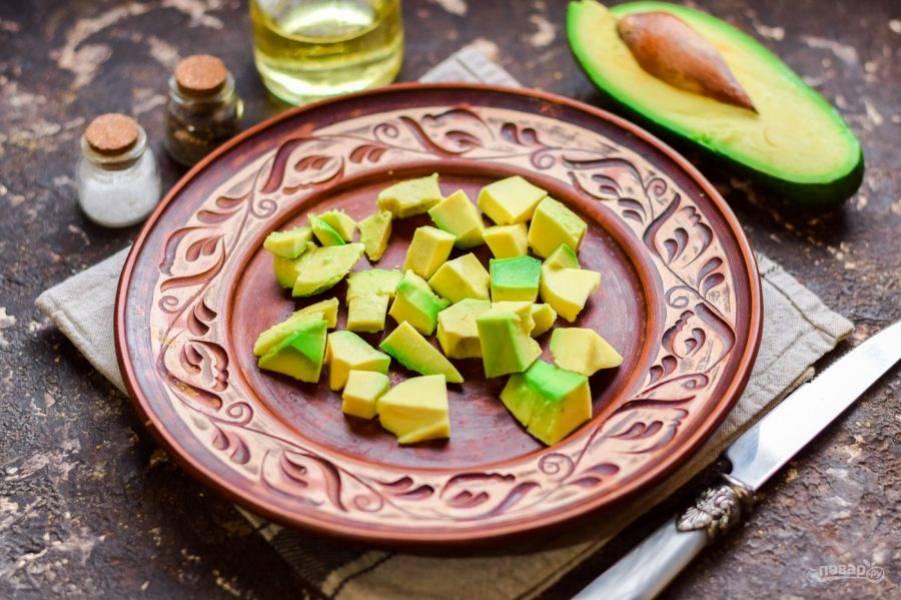 Нарежьте авокадо небольшими кубиками и выложите на салатник.