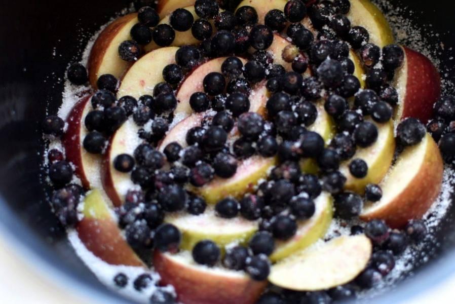 Смазанную чашу мультиварки присыпьте несколькими ложками сахара, выложите яблоки по кругу. Сверху рассыпьте смородину. Если ягода замороженная, не размораживайте. Сверху также присыпьте сахаром.