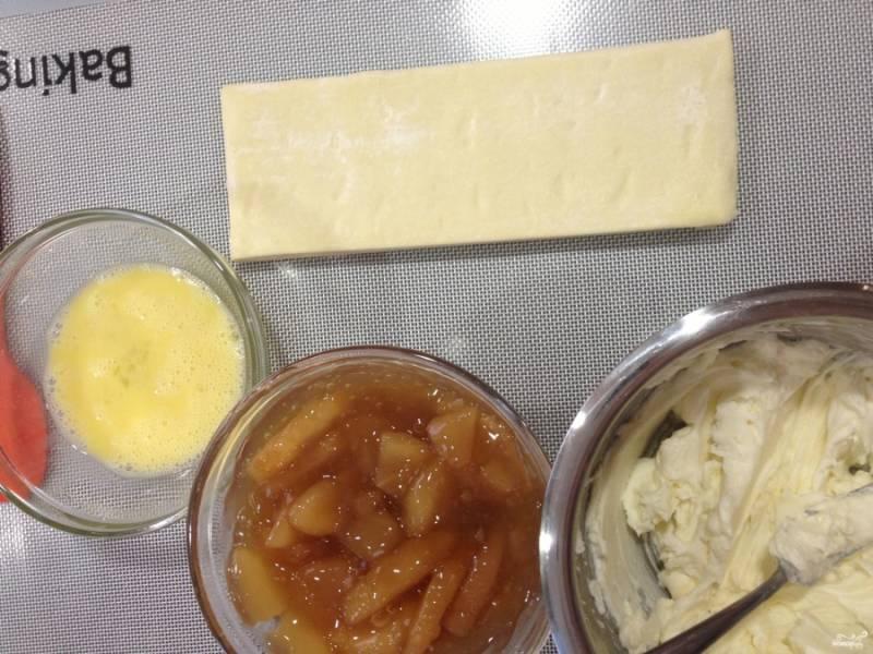 Шаг 1. Разогрейте духовку до 200 градусов. Заранее розморозьте тесто. Положите его на пергамент на противень.