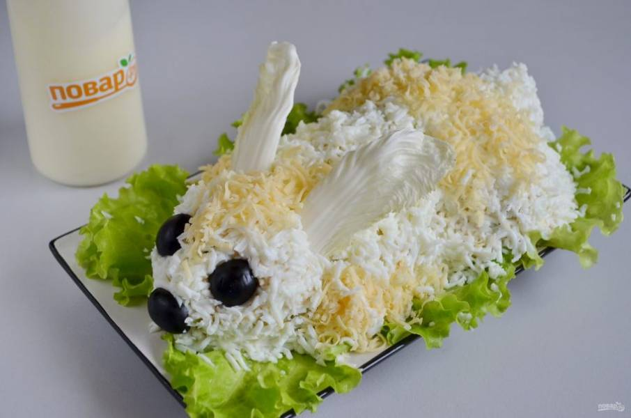 9. Сверху сделайте шубку кролику из тертых белков. Из сыра — пятнышки, глазки и носик — половинки оливок черных, из пекинской капусты — ушки. Пасхальный кролик готов! Дайте ему немного постоять в холодильнике перед подачей.