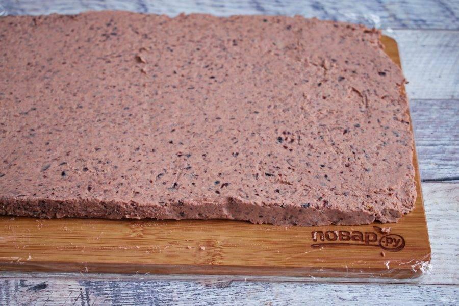 На плоской рабочей поверхности разместите пищевую пленку. И при помощи лопатки разровняйте паштет в прямоугольный пласт, толщиной 1 см.