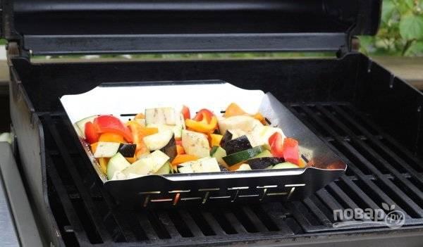 4. Посолите, поперчите овощи, добавьте масло и перемешайте. Выложите в корзинку и поставьте на гриль. Жарьте около 12 минут, каждые минутки 3 перемешивая.