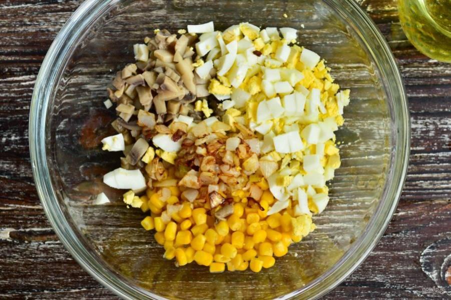В миску выложите консервированную кукурузу, маринованные грибы, нарезанные яйца, жареный лук. Добавьте соль.