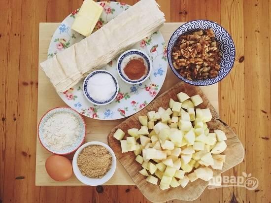 Подготовим ингредиенты. Тесто разложим на столе, пусть размораживается. Яблоки очистим и нарежем кубиками со сторонами примерно 1см.