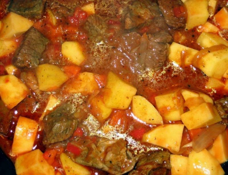 5. Протушив на слабом огне говядину с овощами, отправьте нарезанный кубиками картофель. Накрывайте крышкой и доводите до готовности (в среднем это занимает около часа).