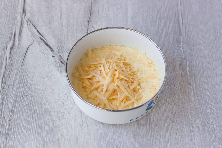 Сыр натрите и добавьте к яйцам. Перемешайте.