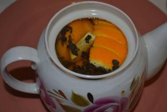 3. Ошпарьте чайник кипятком, отправьте туда зеленый чай, апельсин и нарезанный имбирь. Теперь залейте горячей водой, закройте.