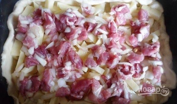Выложите мясо с луком. Закройте всё оставшимся тестом. Посередине сделайте дырку. Взбейте желток с молоком. Покройте смесью тесто.