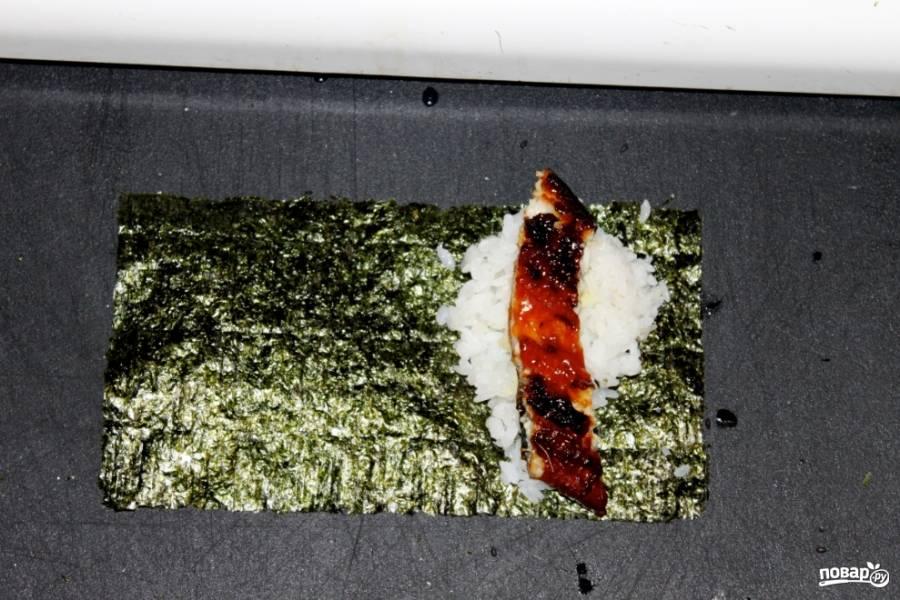 Листья нори поделите на количество роллов.  С одного края выложите остывший рис, смажьте его васаби, сверху - кусочек угря.