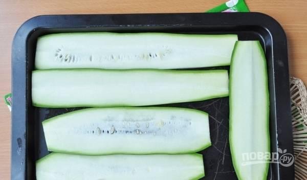 Смажьте противень растительным маслом. Духовку разогрейте до двухсот градусов. Затем вымойте и нарежьте кабачок на тонкие кусочки (в длину). Выложите овощ на противень, запекайте семь минут до мягкости.