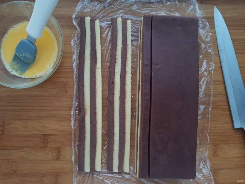 Теперь нарежьте тесто на полоски толщиной в один сантиметр. Полученные полоски снова промажьте яйцом и, чередуя стороны со светлым и шоколадным тестом, соберите брусок из четырех пластов.