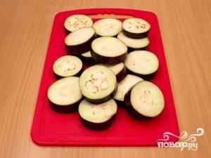 Баклажаны хорошо помойте и нарежьте кружками по 1 см. в толщину. Потом хорошо посолите их и оставьте в миске на полчаса. Затем смойте соль.