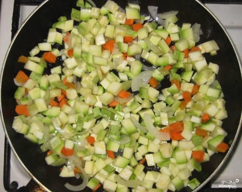 Очистите остальные овощи: морковь, кабачок и репчатый лук. Кабачок и лук нарежьте некрупно, а морковь натрите на крупной тёрке. В сковороду налейте немного растительного масла, обжарьте на нём овощи около 5-8 минут.