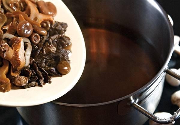 Достаньте из воды отварные белые грибы, измельчите их. Нарежьте маринованные грибочки. Все эти ингредиенты положите в процеженный через марлю бульон.