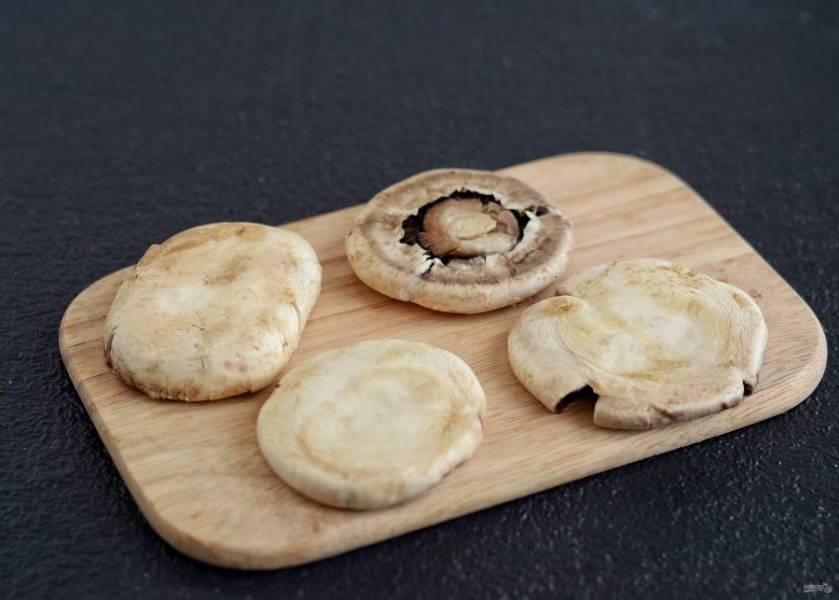 Раздавите шляпки грибов между двух разделочных досок до плоских стейков.