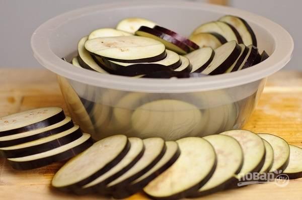 1. Для начала вымойте, обсушите и нарежьте колечками баклажаны. Выложите их в подсоленную воду, пусть полежат какое-то время, чтобы ушла горечь.