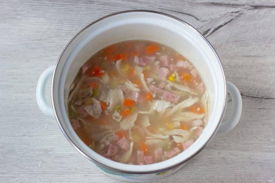 Нагрейте бульон на медленном огне и помешивайте до полного растворения желатина. Доводить до кипения не нужно. Когда желатин растворится, добавьте в бульон курицу, ветчину, морковь, горошек и кукурузу. Перемешайте.
