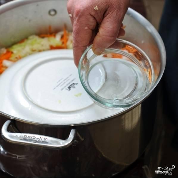 Аналогично выкладываем еще два слоя. Хорошенько спрессовываем содержимое кастрюли кулаком, накрываем тарелкой. Наливаем в кастрюлю полчашки теплой кипяченой воды.