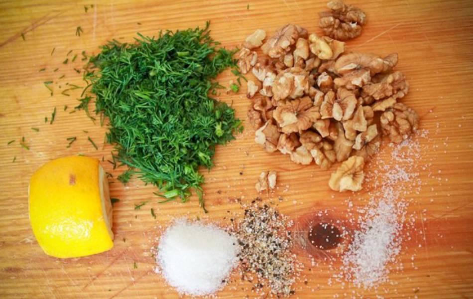 Приготовим ореховый соус. Смешиваем: измельченные орехи, зелень, соль, сахар и специи. Добавляем немного лимонного сока и воду, перемешиваем до однородности.
