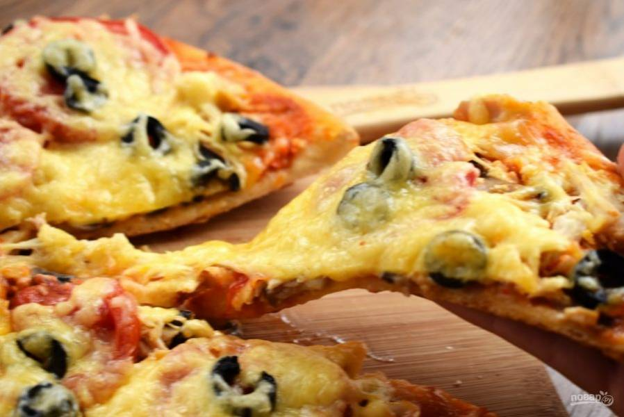 Готовую пиццу переместите на деревянную доску. Разрежьте с помощью специального ножа или ножниц. И наслаждайтесь!