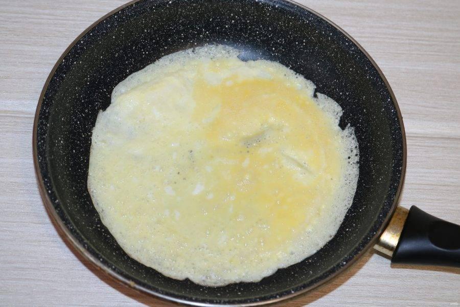 На разогретой сковороде с добавлением небольшого количества масла пожарьте тоненький омлет с двух сторон.