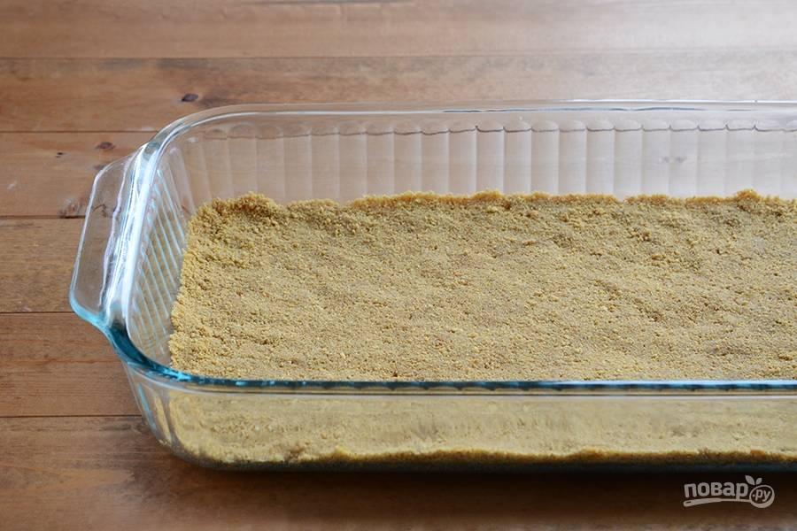 Сделайте тесто. Растопите масло, а потом перетрите его с крошкой от печенья. Распределите тесто по дну формы для выпечки. Выпекайте его при 180 градусах в течение 10 минут. Затем уберите форму в морозилку на 10 минут.