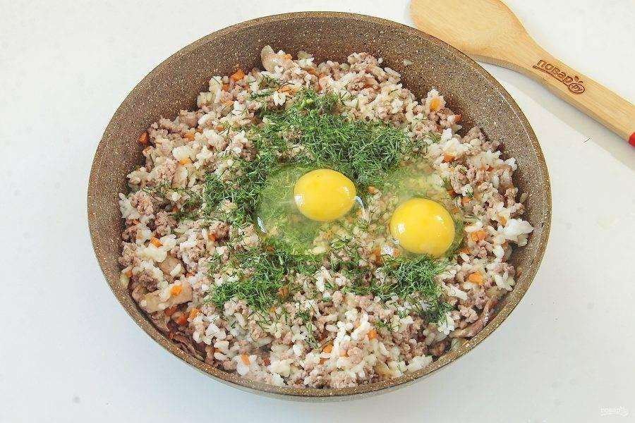 Добавьте отваренный до полуготовности рис. Перемешайте и снимите сковороду с плиты. Дайте немного остыть. Добавьте измельченную зелень и два яйца.